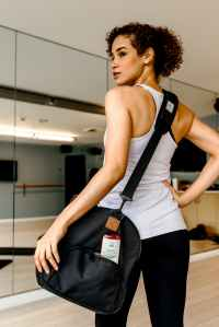 woman in white tank top and black pants carrying black sling bag